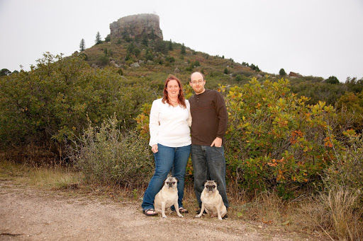Animal Dental Care and Oral Surgery Castle Pines - a couple standing outdoors with their two pugs